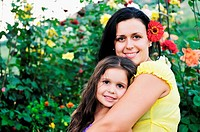 beautiful mom and daughter outdoor in garden together with flower have fun and hug