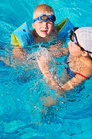 happy kids have fun on outdoor swimming pool at beautiful aquapark