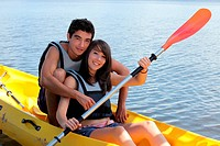 young man and woman doing canoe on a lake