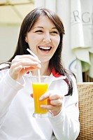 young woman drink juice outdoor in bright restaurant garden at spring
