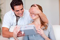 Man covering the eyes of his girlfriend while giving her a present
