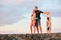 romantic couple in surf wear posing at beach on sunset at summer season