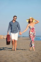 couple on beach with travel bag representing freedom and funy honeymoon concept