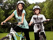 Two happy smiling children in cycling helmets on their bicycles in a park, brother and sister, 10 and 13