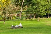 a woman reads in the VanDusen Garden in Vancouver, BC, Canada