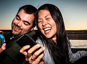 Couple using cell phones outdoors