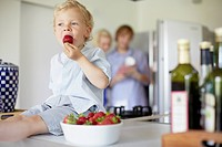 Boy eating strawberries on counter