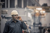 African American worker using cell phone in factory