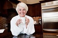 Caucasian woman in robe drinking coffee