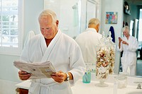 Caucasian man reading newspaper in bathroom