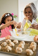African American grandmother and granddaughter baking cookies