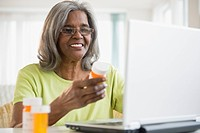 African American woman holding pill bottle and using laptop