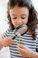 Mixed race girl looking at flower with magnifying glass