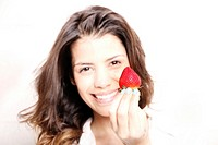 Portrait of a beautiful, latin Woman eating a Strawberry
