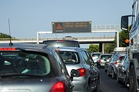 Traffic jam on the French Autoroute in August with warning sign on gantry and slow traffic, France