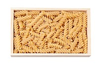 Raw fusilli pasta in a box