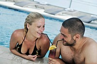 happy young couple in love have fun relax and drink coctail at indoor wellness swimming pool