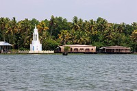 a shrine and moored rice boats, converted to houseboats for tourists, in the Kerala backwaters