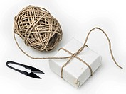 Small parcel, scissors and a spool of string shot on white background. Studio photograph, horizontal frame.