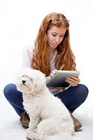 redheaded girl with tablet and dog.