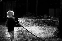 Young boy playing with a watering hose in a garden, with backlighting, Berlin, Berlin, Deutschland