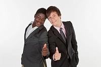 Two young businessmen standing back to back and making a thumbs-up gesture