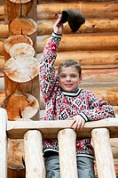 Boy standing on deck of log cabin, waving hat at camera, portrait