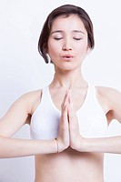 Young Asian woman meditating with hands clasped against white background