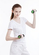 Portrait of young Caucasian woman exercising with dumbbells against white background