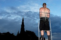 Acrobat tied with chains acting in Princes street of Edinburgh, infront of the scott monument, during the 2007 editon of the fringe festival