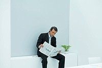 Mature businessman reading newspaper in office