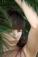 Young woman behind palm frond, looking down, portrait
