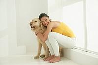 Hispanic woman hugging dog