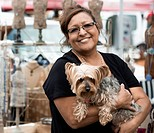 Hispanic woman holding dog at flea market