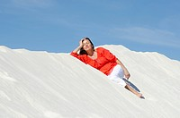 Pretty woman lying relaxed on sand dune