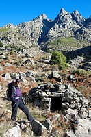 Hiker next to a old hut and Chilla Peak, in Tejea Valley in Sierra de Gredos Regional Park  Candeleda  Ávila province  Castilla y León  Spain