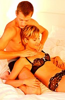 Couple in bed giving themselves sensual massages.