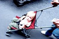 18 months old baby girl in a baby stroller.