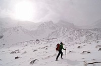 A mountaineer cross a snow field on mountains during a storm, Pe&#241;a Ubi&#241;a, Parque Natural Ubi&#241;as-La Mesa, Asturias, Spain