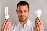 Man holding a low energy bulb at left and a regular bulb at right.