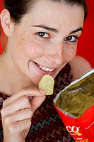 Woman eating potato chips.