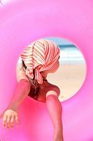 Little girl at the beach holding rubber ring
