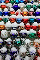 collection of colored glass balls decoration in garden in winter with snow