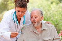 nurse or doctor taking temperature of senior patient