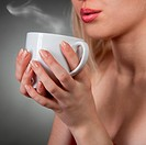 woman holding hot cup and blowing on it