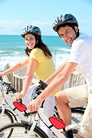 Young man and young woman having bike ride