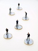 Businessmen figurines over euro coins.