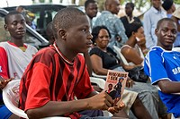 Abuja, Nigeria: June 14, 2008. A male youth holds a brochure about HIV/AIDS and sex while listening to a behavior change communication session about H...