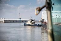 Tugboat pulling ship in urban harbor