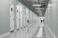 Hallway and prison cells along a corridor. Observation hatches in the doors. A Correctional Facility. A desk and table at the end
